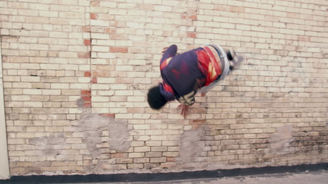 vidéos et rushes de young man doing parkour on the street - mur brique