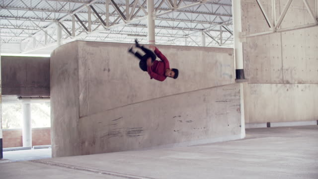 stockvideo's en b-roll-footage met ws young man doing parkour tricks off a wall - cement