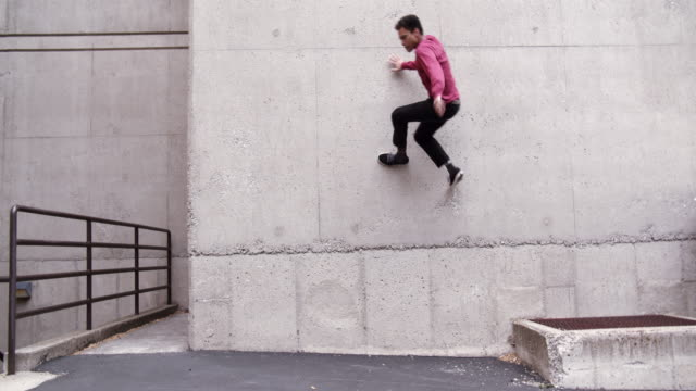 stockvideo's en b-roll-footage met young man doing parkour tricks outdoors - cement