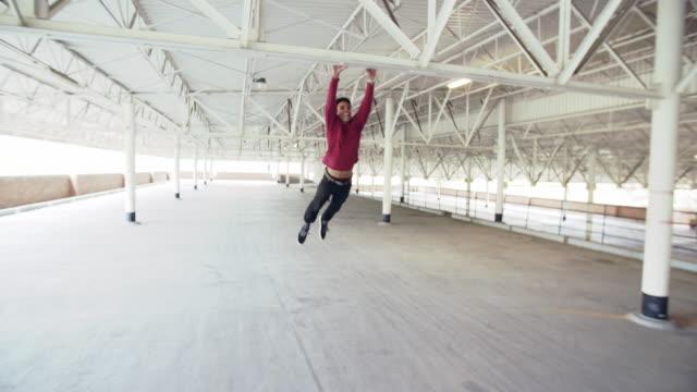 vidéos et rushes de ws young man doing parkour tricks - se balancer