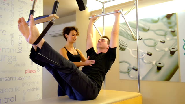 dolly: young man doing pilates exercise with instructor - pilates stock videos and b-roll footage