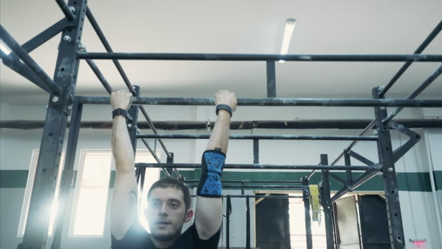young man doing pull ups on horizontal bar. - horizontal bar stock videos and b-roll footage