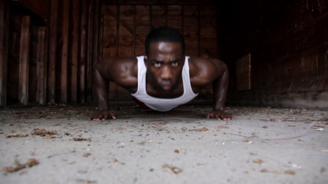 CU Young man doing push-ups inside  garage while working out / Minneapolis, Minnesota, United States