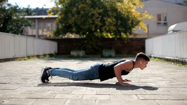 young man doing push-ups outdoors - bodyweight training stock videos & royalty-free footage