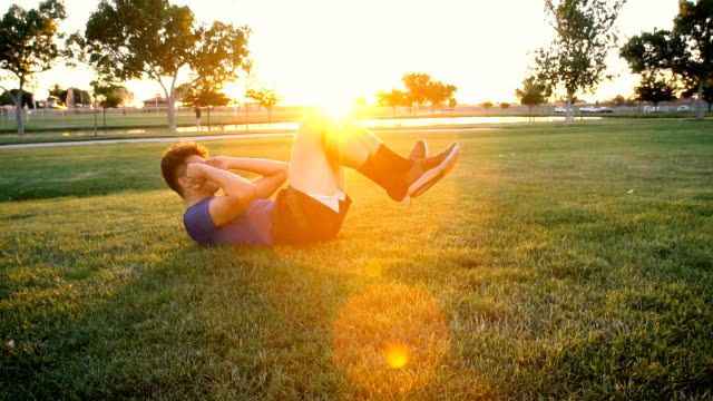 Young Man Doing Situps in the Park at Dusk Slow Motion
