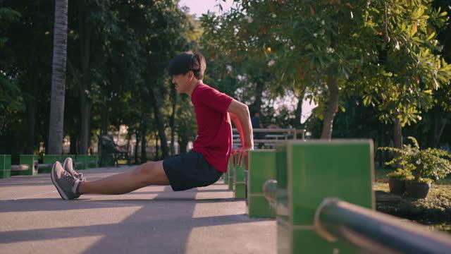 vídeos de stock, filmes e b-roll de jovem fazendo exercício de alongamento no parque - calções de corrida