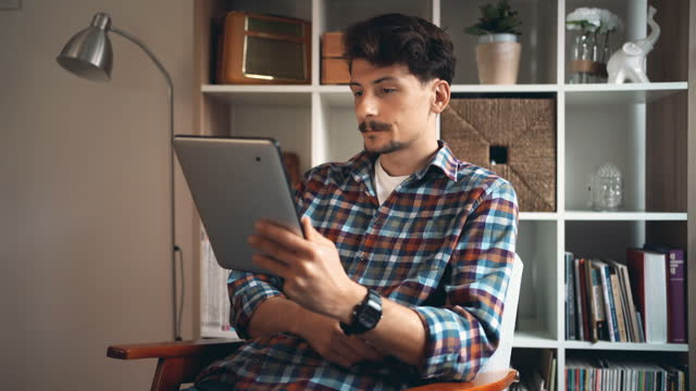 young man doing video call on a digital tablet at home - tartan stock videos & royalty-free footage