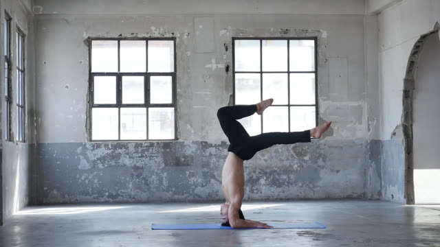 A young man doing yoga headstand pose indoors