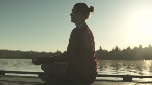 A young man doing yoga on a dock at sunrise