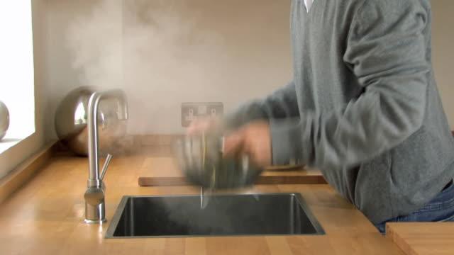 MS TU Young man draining pasta / Hackney, United Kingdom