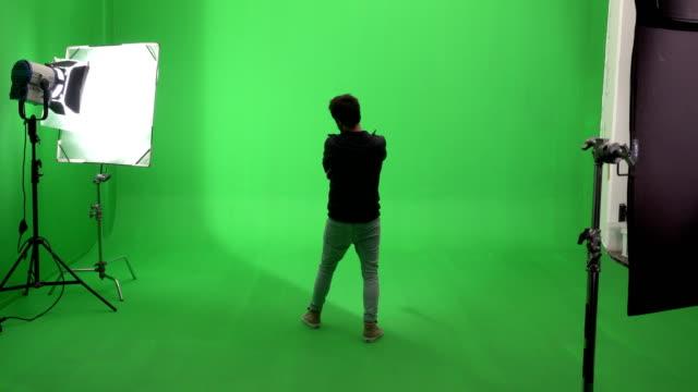 vídeos de stock e filmes b-roll de young man drawing graffiti on green screen studio - grafite produto artístico