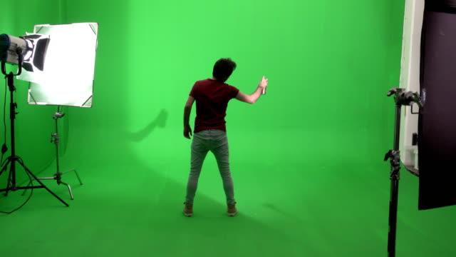 グリーンスクリーンスタジオで落書きを描く若い男 - 壁画点の映像素材/bロール