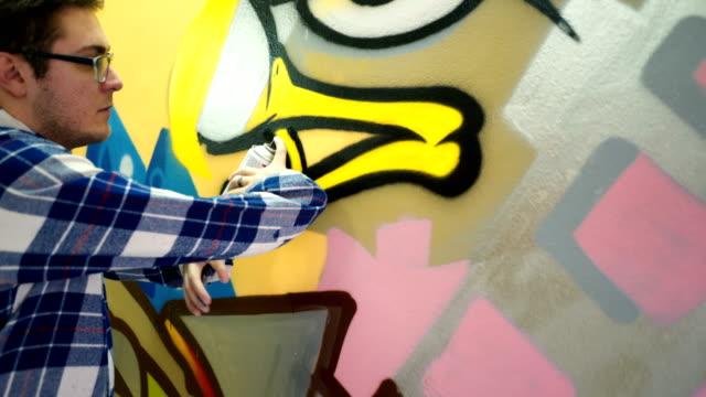 giovane che disegna graffiti - sfondo multicolore video stock e b–roll