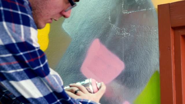 vídeos y material grabado en eventos de stock de hombre joven dibujando graffiti - arte decorativo