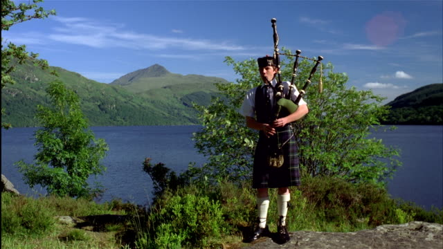 vídeos de stock, filmes e b-roll de wide shot young man dressed in traditional clothing  plays bagpipe with loch lomond and highlands in background, central scotland - escócia