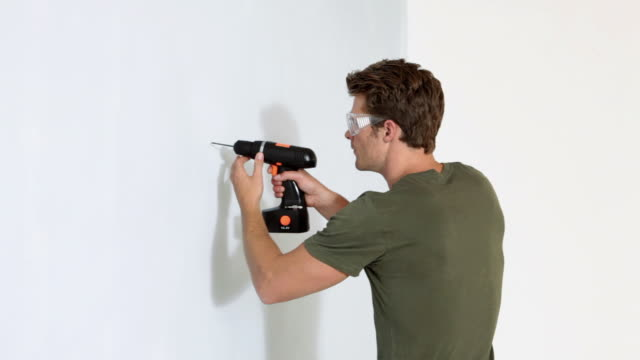 Young man drilling a hole in a wall