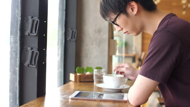 young man drinking coffee and using tablet - coffee drink stock videos & royalty-free footage