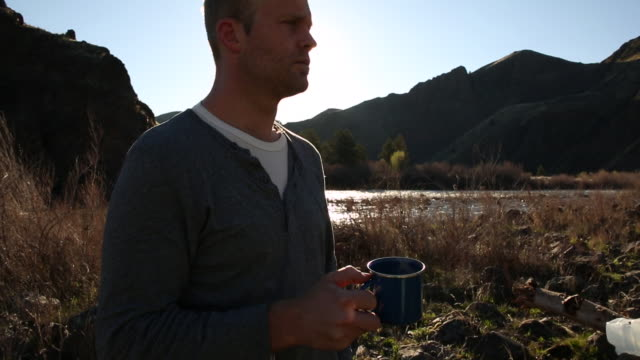 A young man drinking coffee from a cup while camping outdoors near a river.