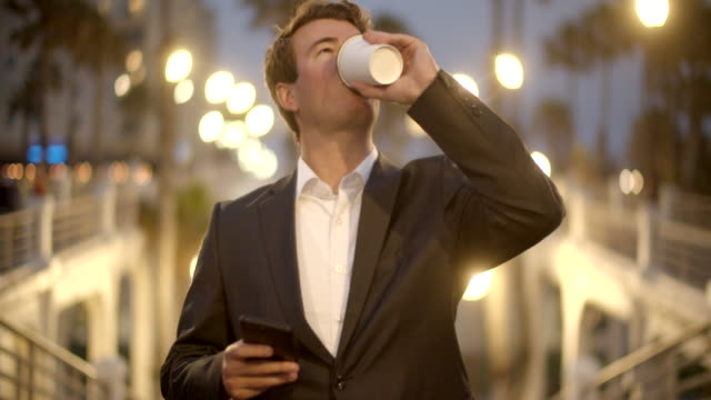 ms young man drinking coffee on the street at night - caffè bevanda video stock e b–roll