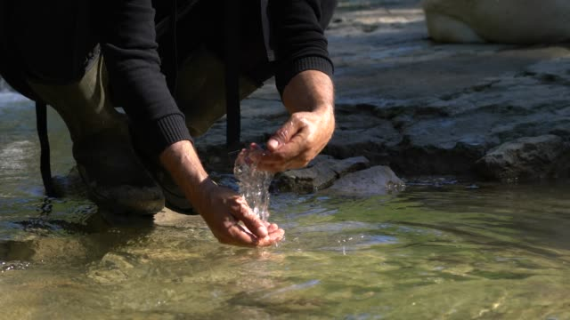 Young man drinking fresh water from mountain river