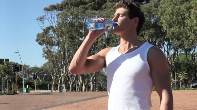 vidéos et rushes de young man drinking mineral water - seulement des jeunes hommes