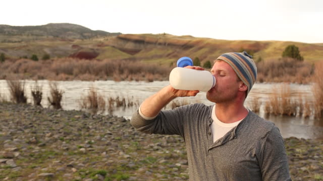 a young man drinking water and coffee while camping outdoors near a river at sunset. - hügelkette stock-videos und b-roll-filmmaterial