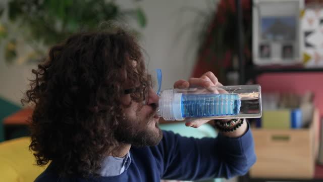 ung man dricksvatten från återanvändbar flaska - vattenflaska bildbanksvideor och videomaterial från bakom kulisserna