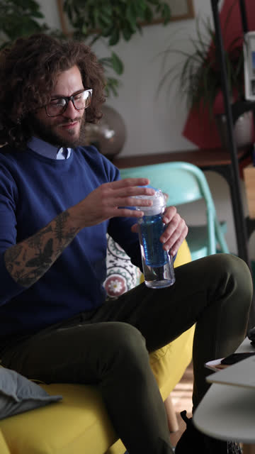 young man drinking water from reusable bottle - bottle stock videos & royalty-free footage