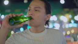 Young man drinking wine at rooftop barbecue party