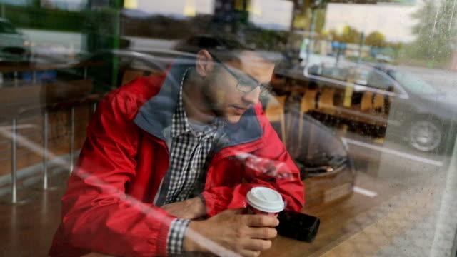 vidéos et rushes de jeune homme café boissons dans une station-service - station service