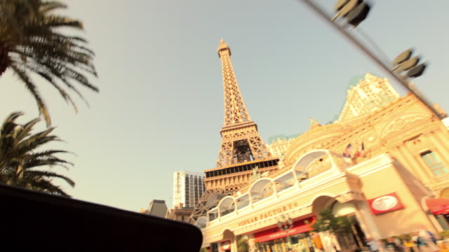 a young man drives a convertible past the replica of the eiffel tower outside the paris hotel and casino in las vegas. - replica eiffel tower stock videos & royalty-free footage