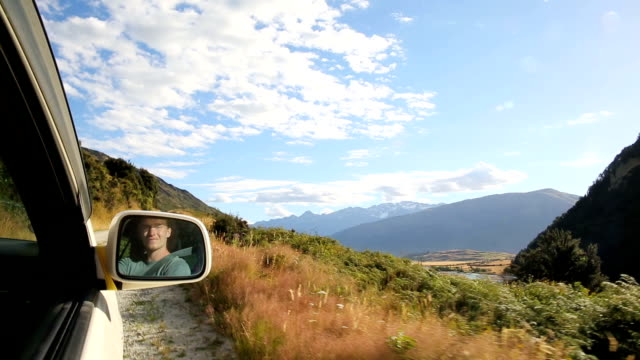 Young man drives down 4x4 road admiring mountain view along the way