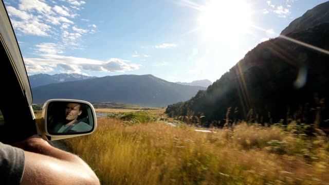 young man drives down 4x4 road admiring mountain view along the way - wing mirror stock videos & royalty-free footage