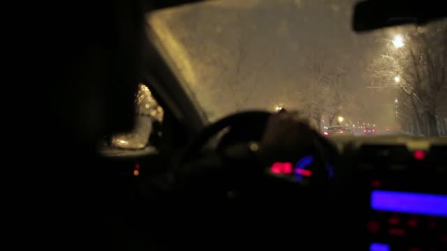 Jonge man het besturen van een auto in de nacht tijdens een sneeuwstorm.