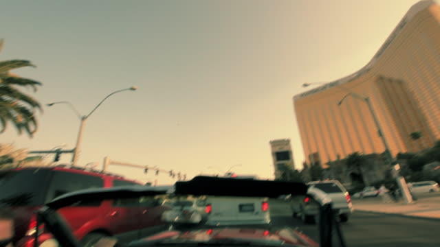 a young man driving a convertible waits in traffic near a high-rise hotel in las vegas. - オープンカー点の映像素材/bロール