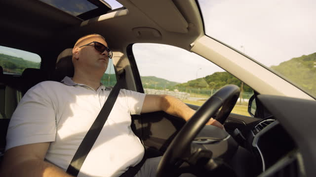 stockvideo's en b-roll-footage met young man driving car on a sunny day - sunny