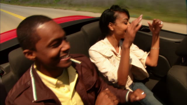 MS PAN Young man driving convertible through rural wine country while happy couple dances in backseat / Paso Robles, California, USA