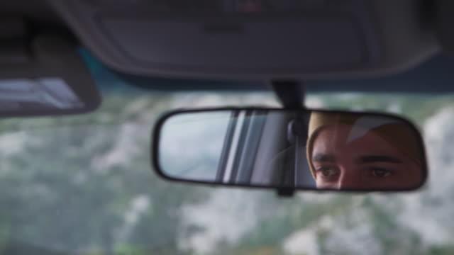 Young man driving through mountains through rear mirror