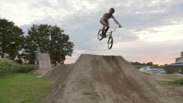 a young man dropping in on a start ramp riding his bmx bike bicycle on an outdoor dirt track with jumps. - bicycle trail outdoor sports stock videos & royalty-free footage