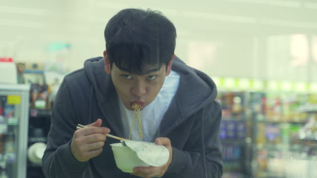a young man (the jobless) eating an instant noodle in a convenience store - 麺点の映像素材/bロール