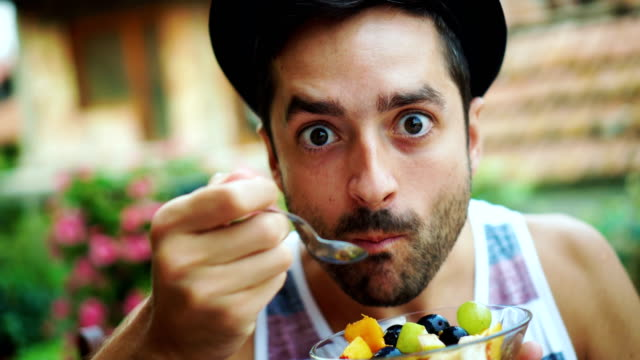 junger mann essen obstsalat - dieting stock-videos und b-roll-filmmaterial