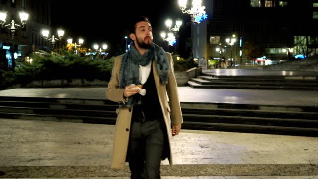 stockvideo's en b-roll-footage met jonge man buiten eten - following moving activity