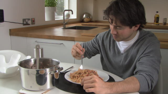 ms pan young man eating pasta / hackney, united kingdom      - pasta video stock e b–roll
