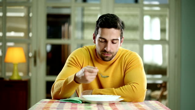 Young man eating soup