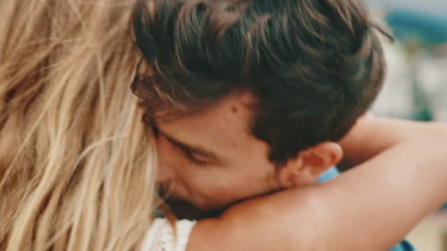 young man embracing girlfriend at beach - human hair stock videos & royalty-free footage