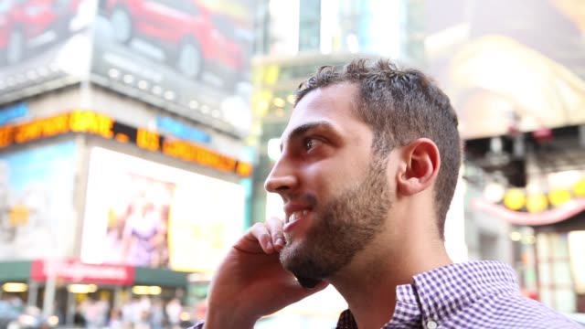 young man enjoying a great time while talking on the phone in times square, manhattan, new york city, usa - times square manhattan stock videos & royalty-free footage