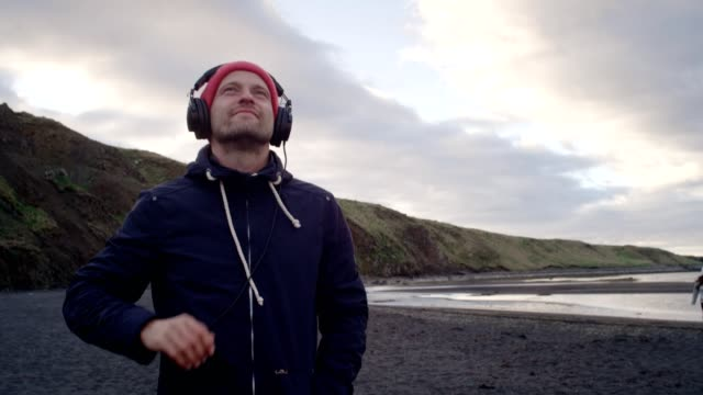 young man enjoying music on a beautiful black beach - eyes closed stock videos & royalty-free footage