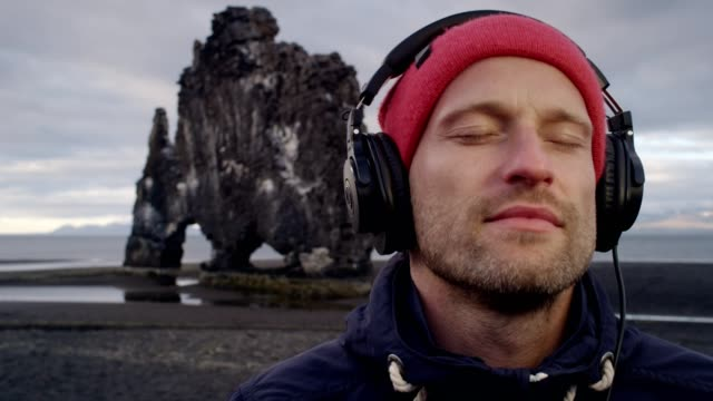 young man enjoying music on a beautiful black beach - woolly hat stock videos & royalty-free footage