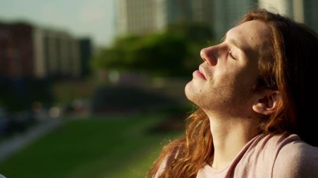 stockvideo's en b-roll-footage met jonge man genieten van zonnige dag - sunbathing