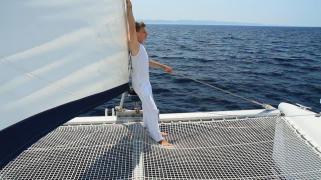 hd: giovane uomo godendo la navigazione - barca da diporto video stock e b–roll